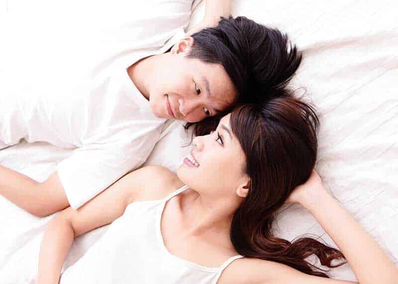 ベッドで見つめあって添い寝する男女